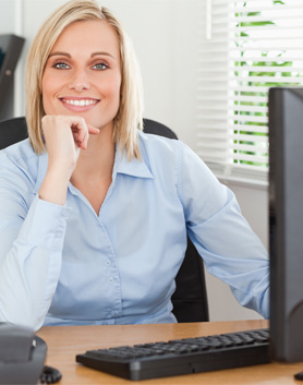 Professional woman sitting at computer desk.